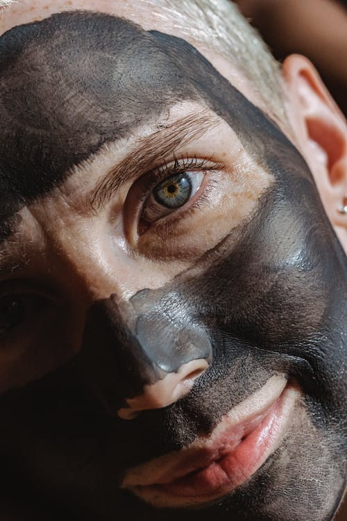 Blue eyed lady looking at camera with dark clay mask applied on face