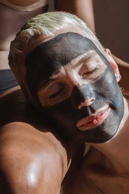 Lady with clay mask on face relaxing on partner leg