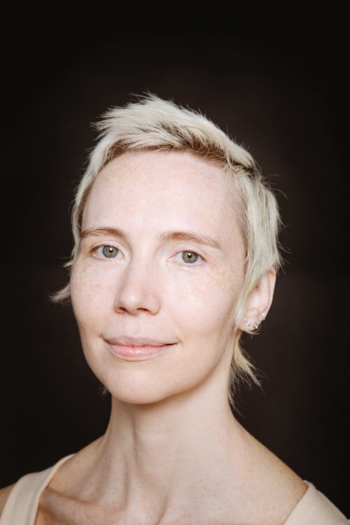 Headshot of woman with short blond hair looking at camera on dark background