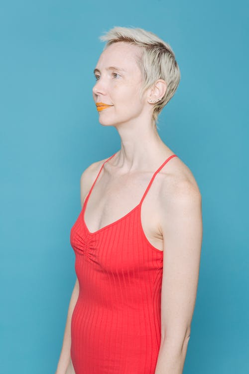 Fair haired woman in red bodysuit standing against blue background and looking away