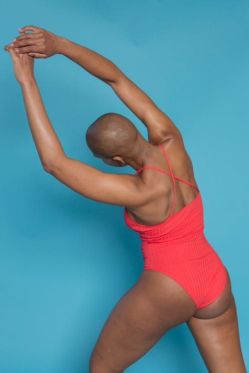 Faceless black female stretching in studio on blue background