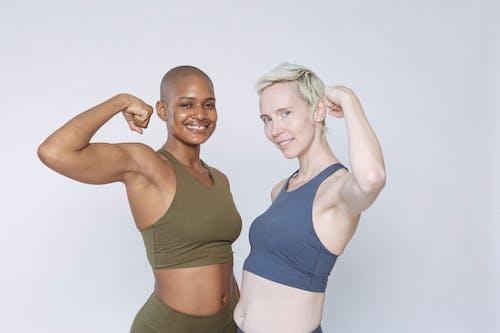 Woman in Blue Sports Bra Beside Woman in Gray Tank Top