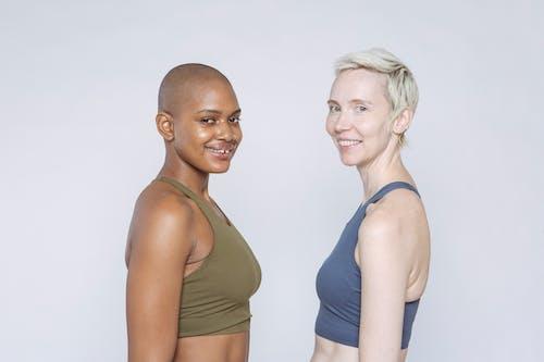 Woman in Blue Sports Bra Beside Woman in Gray Sports Bra