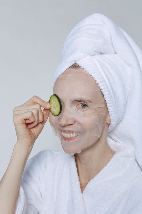 Positive female in white towel on head and bathrobe moisturizing face with sheet mask and slice of cucumber against white background