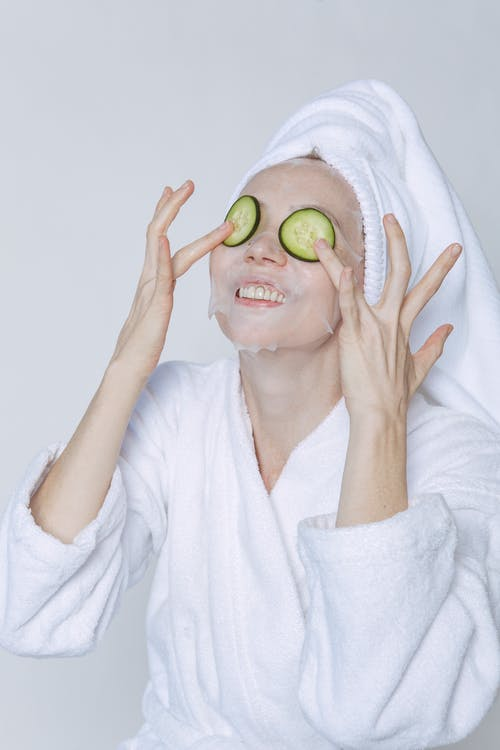 Young female in bathrobe and towel taking care of skin with cucumber and sheet mask against white background