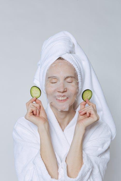 Positive female in white bathrobe and turban holding cucumber slices while moisturizing skin with sheet mask against white background