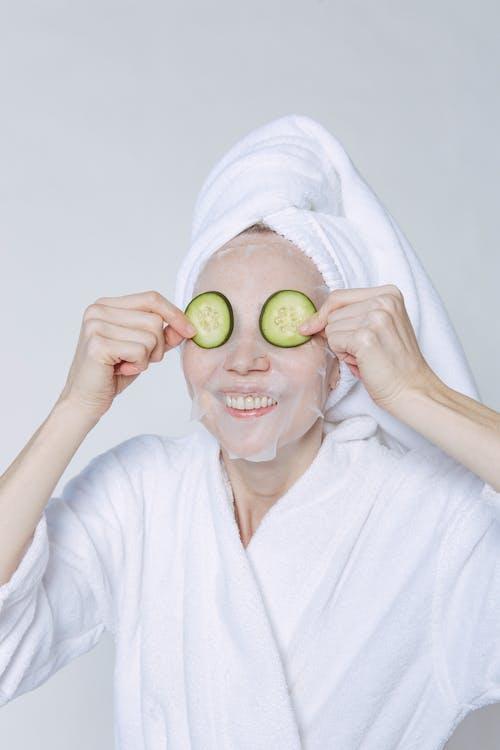 Positive female wearing white bathrobe and towel smiling happily while applying cucumbers on eyes for moisturizing skin against white background