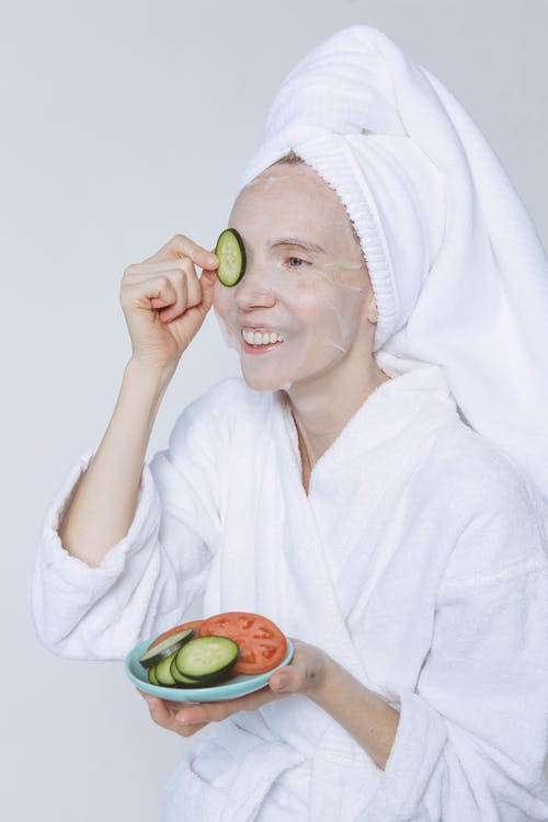 Positive young female in white towel and bathrobe enjoying healthy skin care morning routine with cucumber slices and sheet mask