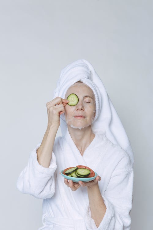 Woman in sheet mask covering eyes with cucumber slices