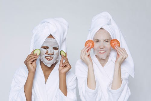 Optimistic multiethnic females wearing towels and bathrobes applying slices of cucumbers and tomatoes for skincare moisturizing treatment