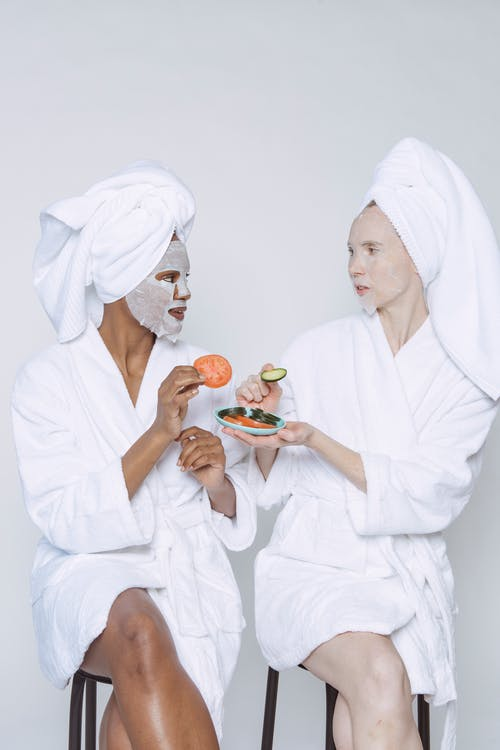 Multiethnic females in bathrobes and towels moisturizing faces with wet sheet masks and taking slices of tomato and cucumber from plate