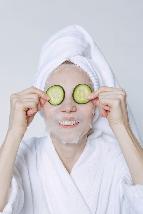 Positive female in towel turban and bathrobe applying cucumber slices on face with sheet mask for skincare treatment