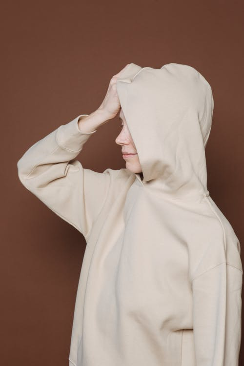 Young female model covering face with hood of oversize sweatshirt while standing against brown background