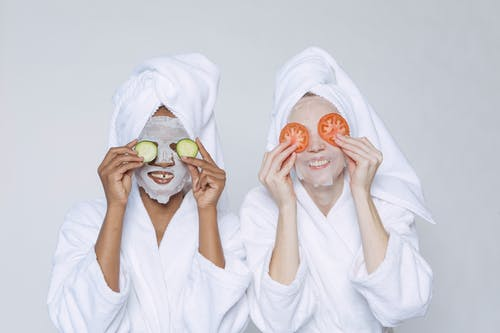 Positive diverse women in bathrobes and turbans moisturizing faces with sheet mask and applying slices of cucumber and tomato on eyes against white background