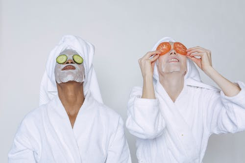 Young multiethnic females wearing bathrobes and towels moisturizing face with masks and slices of tomatoes and cucumbers against white background