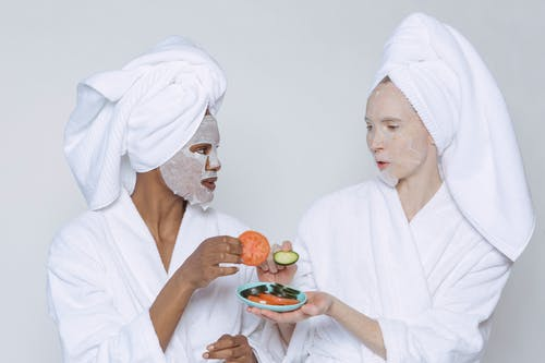 Multiethnic women in sheet masks and towel with bathrobe