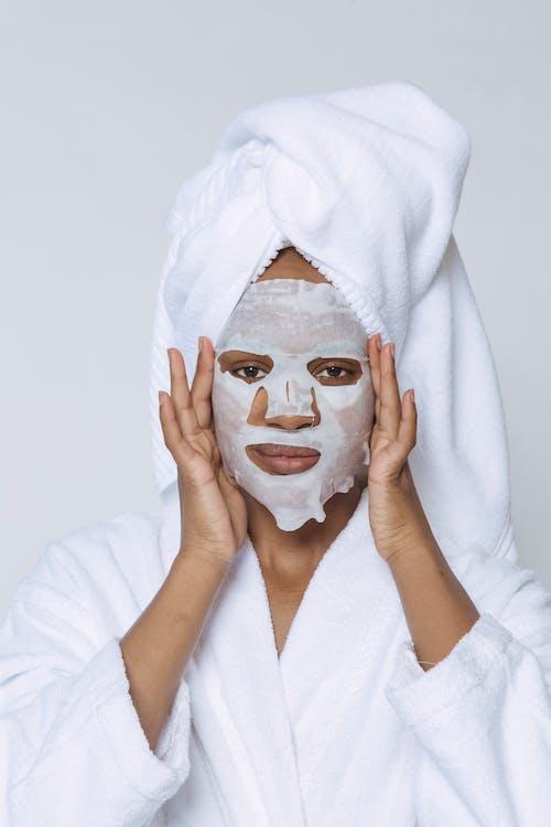 Black woman applying sheet mask in morning