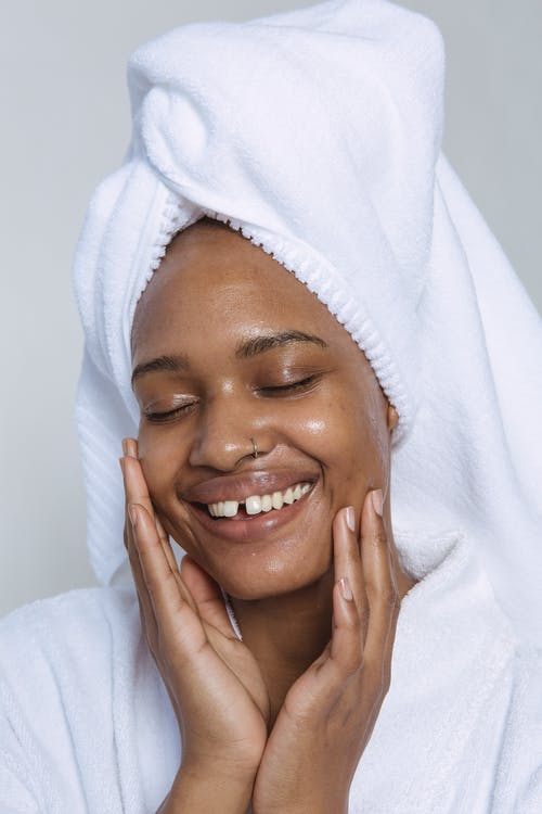 Smiling black woman with closed eyes gently touching face