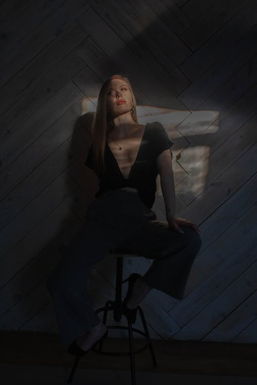 Stylish model with makeup resting on chair in sunbeams