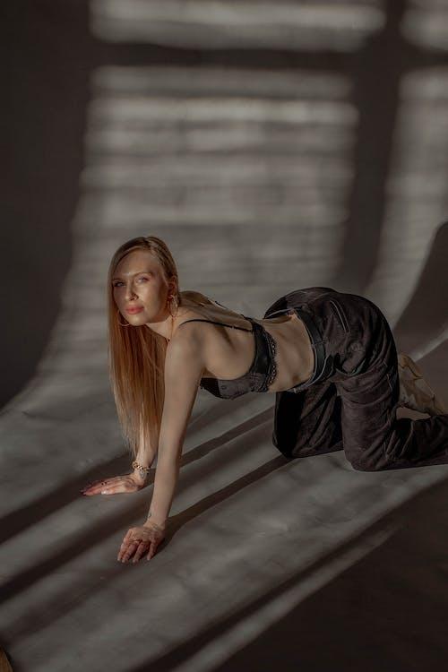 Sensual model in trendy wear on floor with shadows