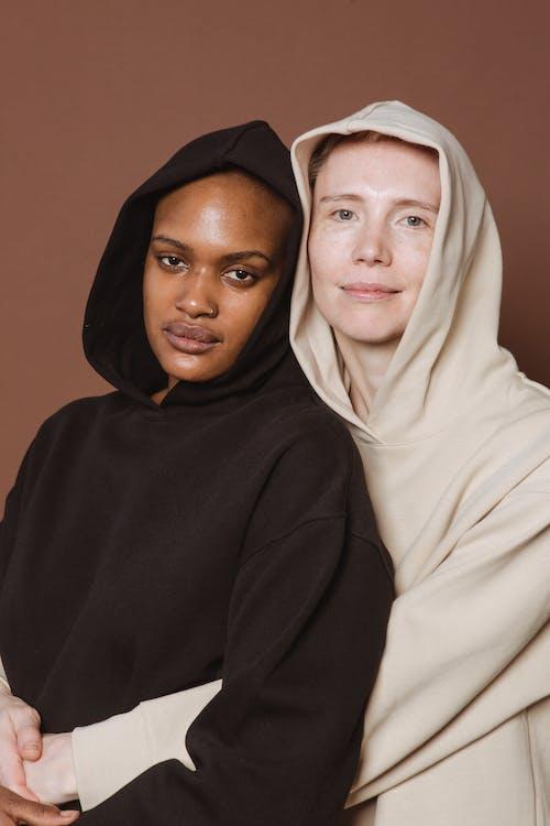 Calm diverse women in hoodies hugging against brown wall