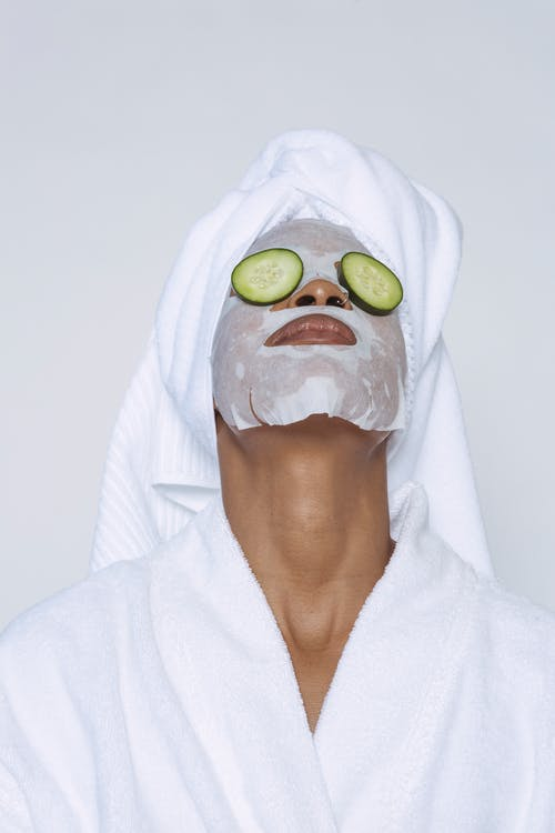 Unrecognizable black female in white bathrobe and towel on head and with sheet mask and cucumber slices on eyes standing head thrown back against white background