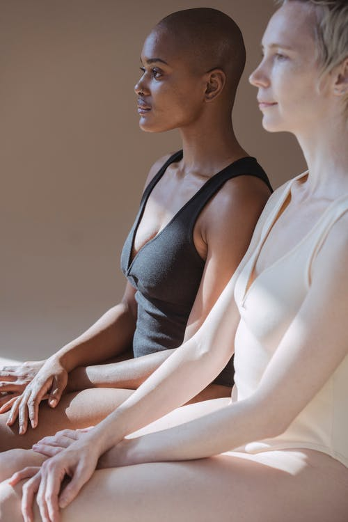 Side view of multiracial females with short hair in contrast bodysuits sitting and looking away while meditating in light studio