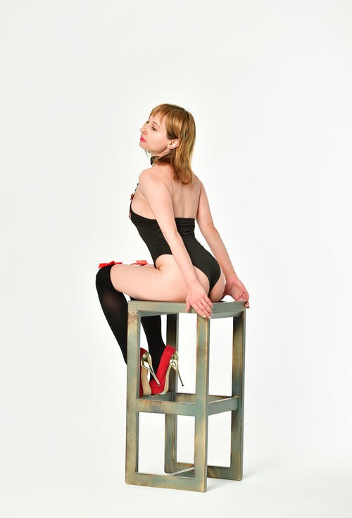 Full body side view of seductive female in underwear and stockings sitting on metal stand on white background in light studio