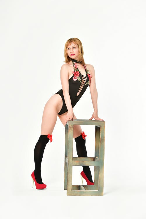 Full body of seductive female in black bodysuit and stockings standing near metal stand on white background in modern studio