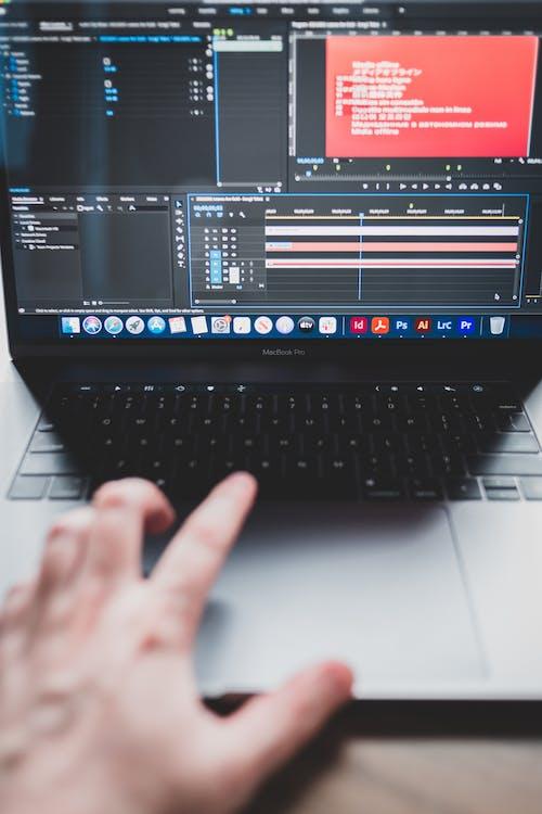 Crop man using laptop while making music