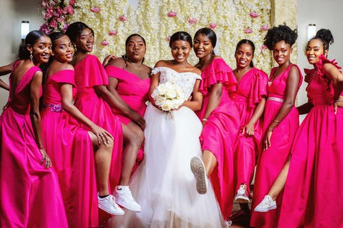 Woman in Bridal Gown with Women in Pink Dresses
