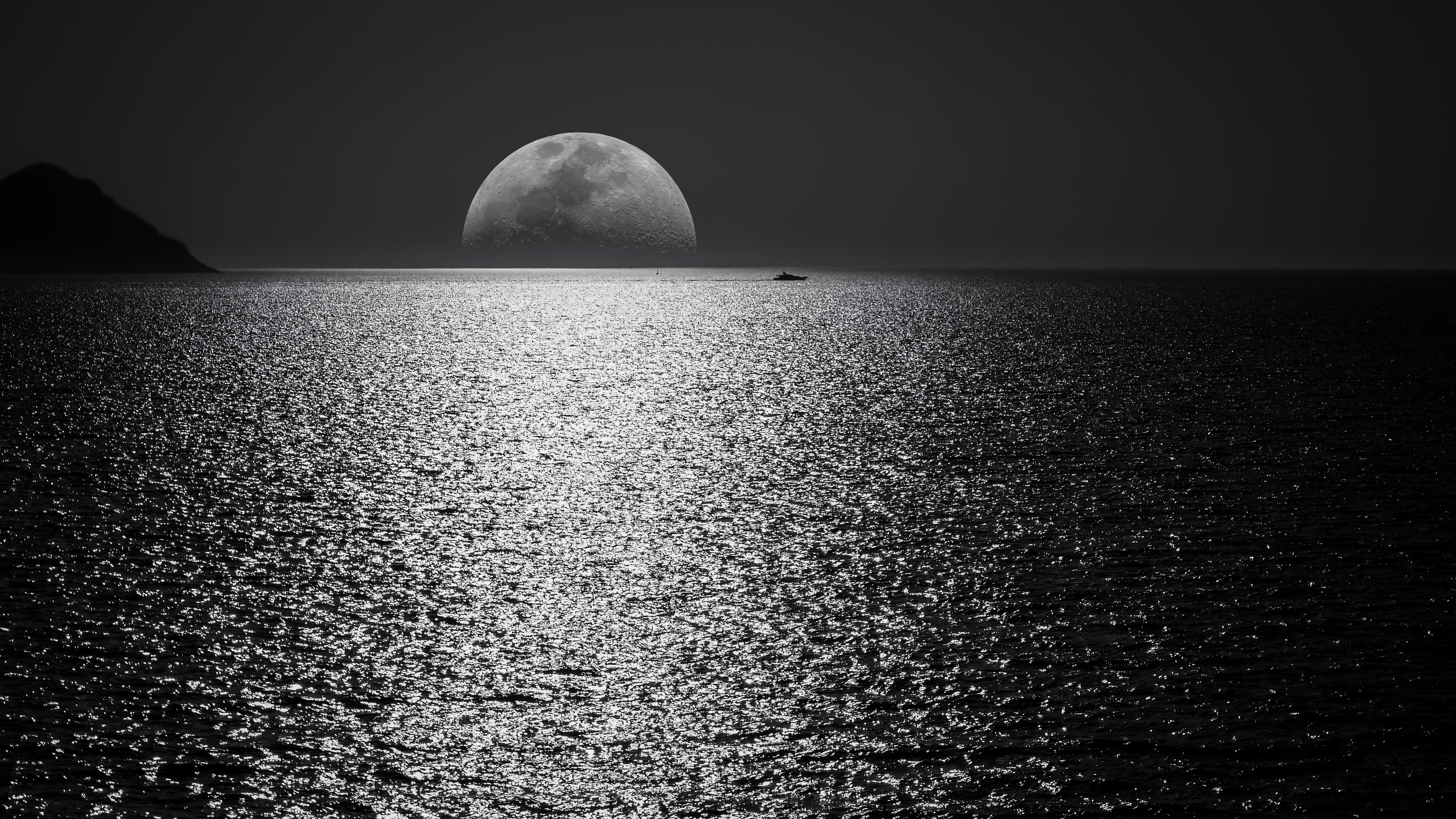white and black moon with black skies and body of water photography during night time