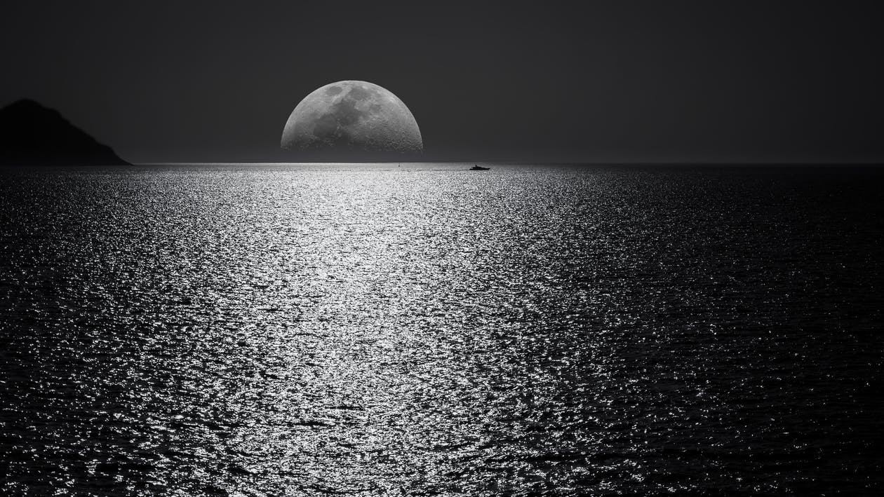 White and black moon with black skies and body of water photography