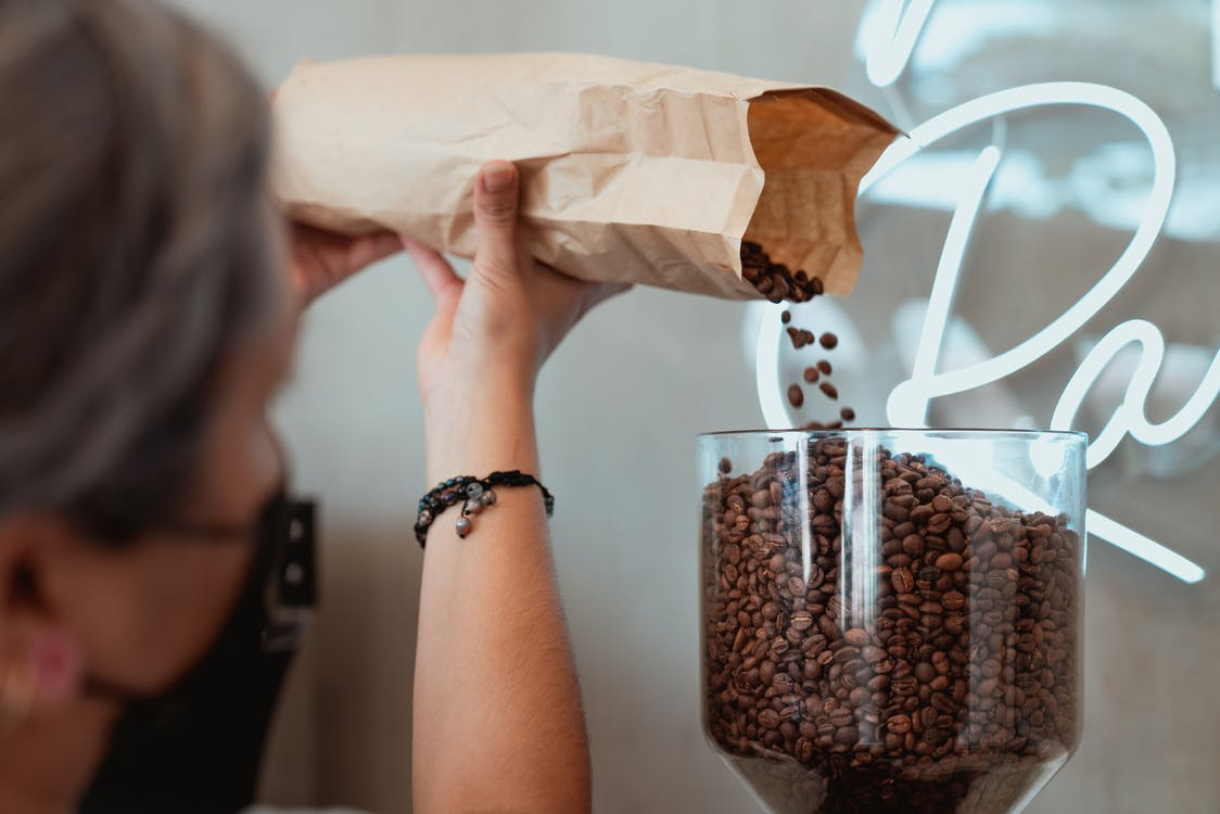 Photo of Barista Pouring Fresh Coffee Beans on Coffee Grinder