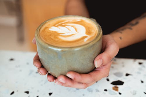 Close-Up Photo of Person Holding Mug of Cappucino