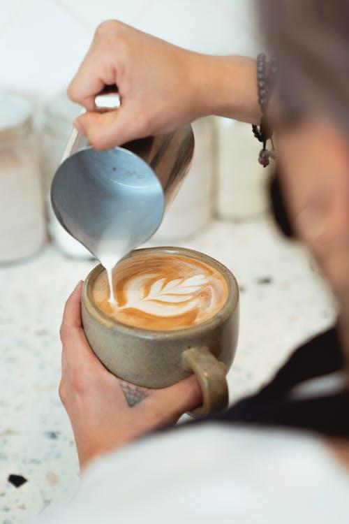 Person Pouring White Liquid on Brown Ceramic Mug