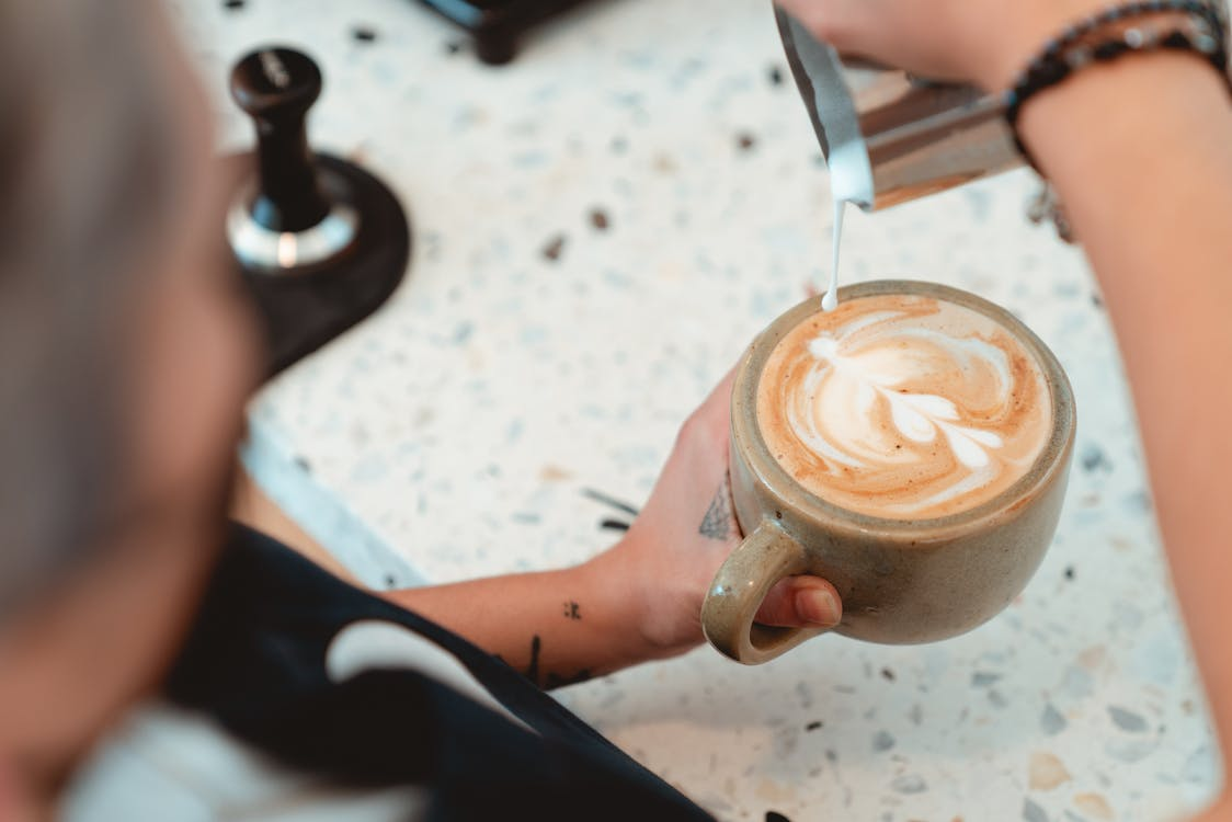 Photo of Barista Pouring Milk on Latte