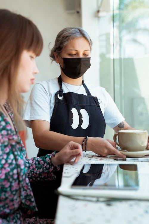 Photo of Employee Serves Coffee to Customer