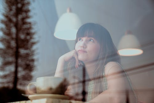 Photo of an Attractive Woman Thinking Inside a Coffee Shop