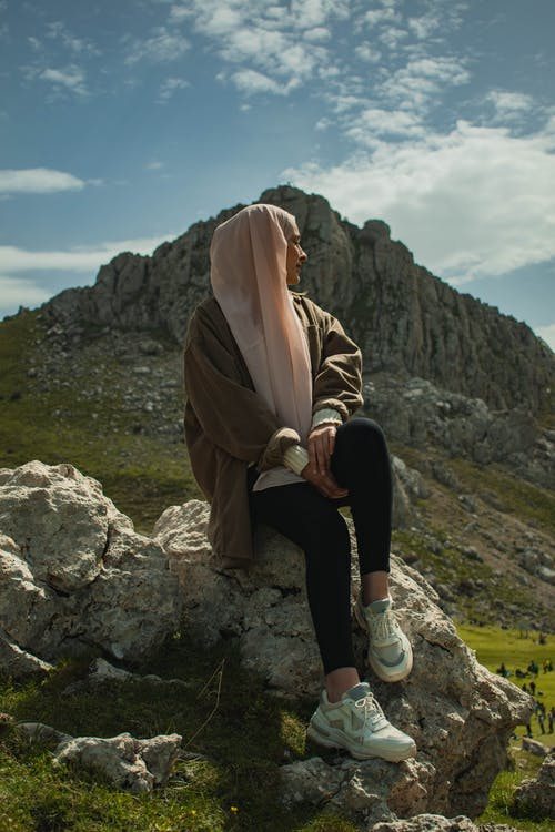Woman in Brown Hijab and Black Pants Sitting on Rock Formation