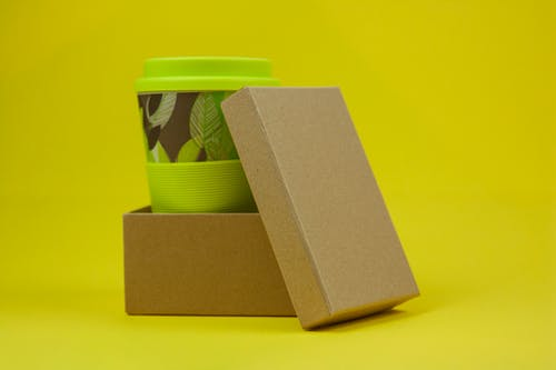 Reusable eco green bamboo cup with leaves in carton box on yellow background in light studio