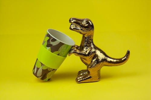 Souvenir dinosaur drinking from mug