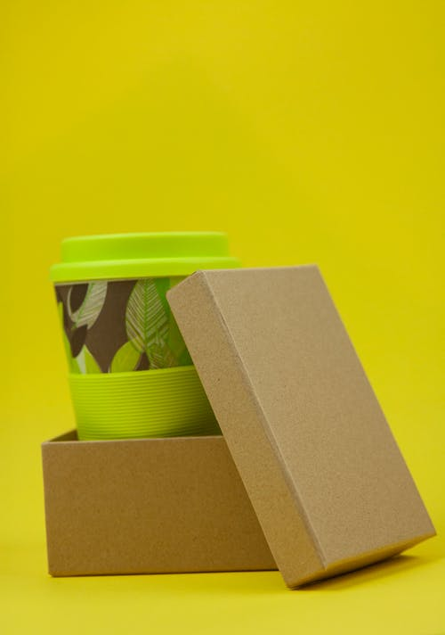 Green cup with lid placed in paper eco friendly box against yellow background