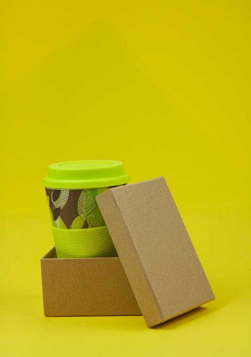 Isolated eco friendly box with lid containing disposable green cup on yellow background