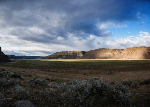 Green Grass Field Near Brown Mountain Under Blue Sky