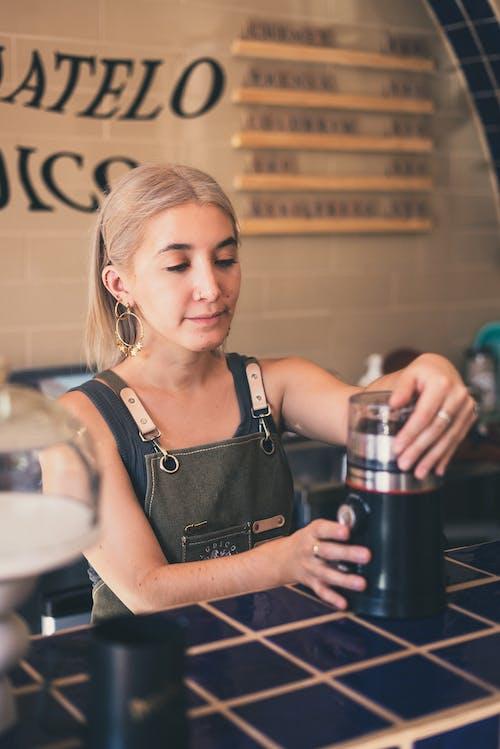 Photo of Barista Using Coffee Grinder