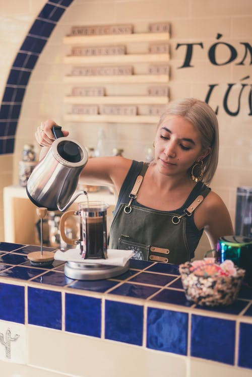 Photo of Barista Pouring Hot Water on French Press