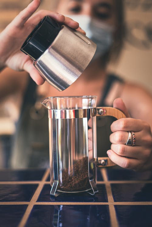 Photo of Person Holding Stainless Cup Pouring Ground Coffee on French Press