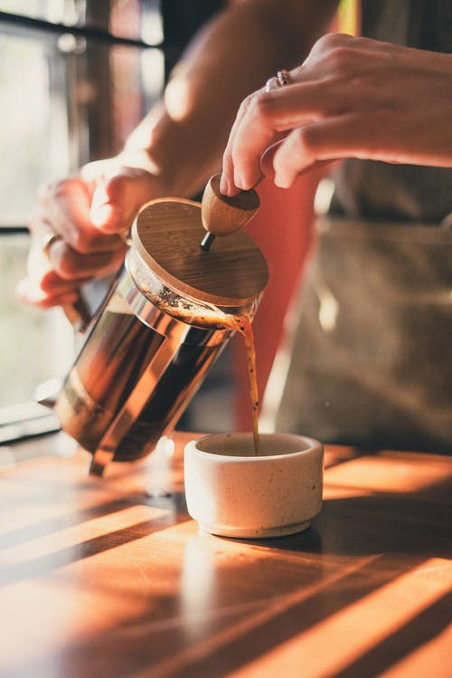 Photo of Person Pouring Brewed Coffee on Ceramic Mug