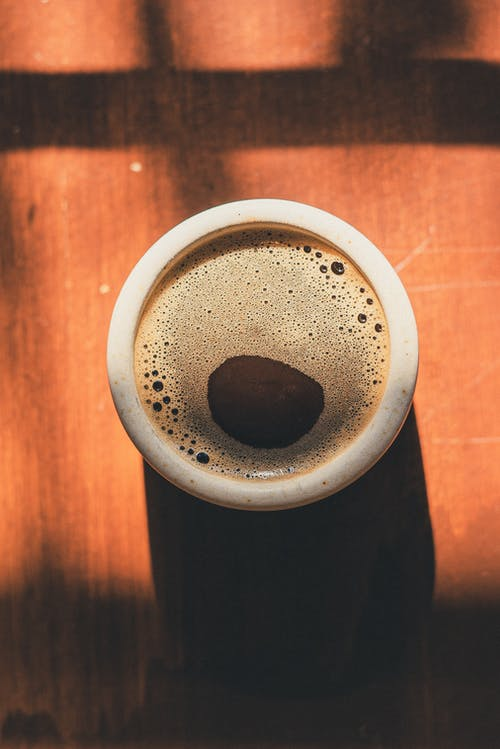 Photo of Cup of Coffee on Top of Wooden Surface